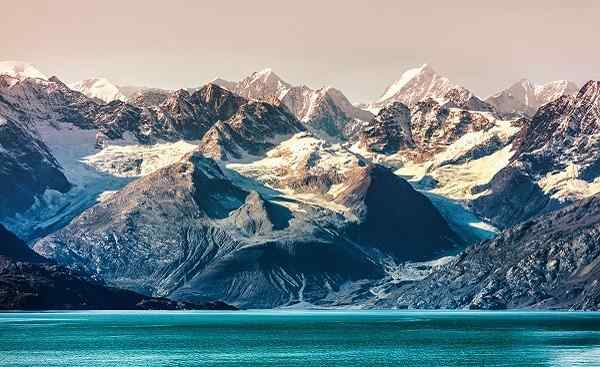 Alaska cruise travel view of snow capped mountains at sunset. Amazing glacial landscape view from cruiseship vacation showing snowy mountain peaks 631031060